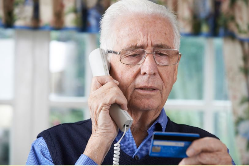 Senior holding credit card on phone