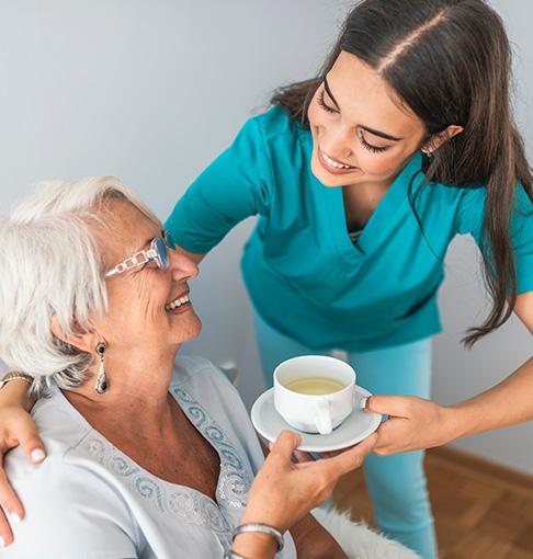 caretaker giving senior tea