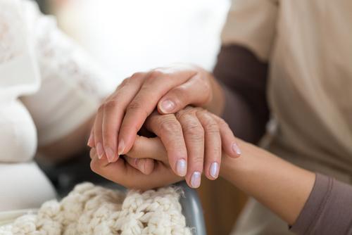 caregiver and senior hands