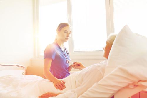 nurse tending to senior in hospital bed