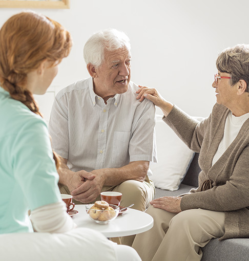 senior woman and man talking with caregiver