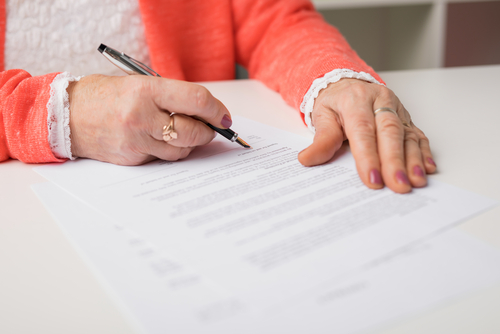 senior woman signing papers