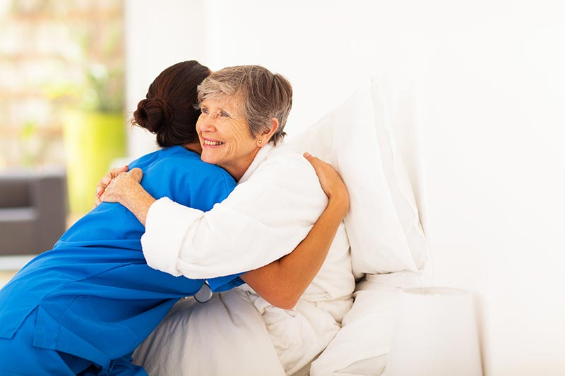 Caregiver and Senior Hugging