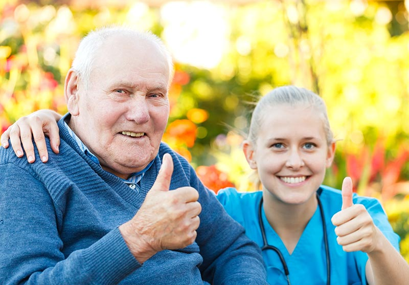 Senior with Caregiver thumbs up
