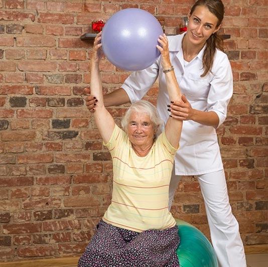 Senior Exercising with Caregiver
