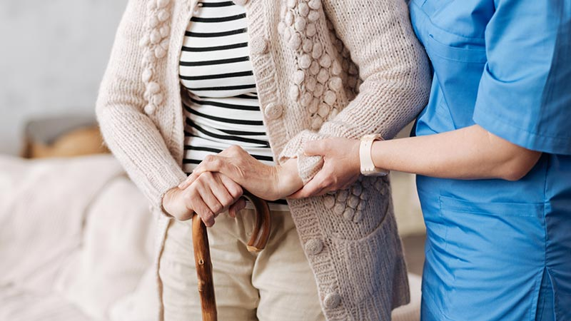 Senior Getting Help from Caregiver
