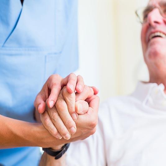 Senior Man Holding Hands With Caregiver