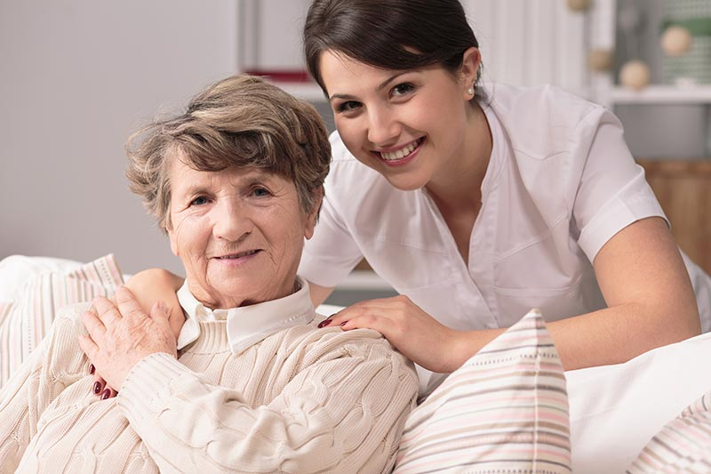 Senior Woman with Caregiver Helping
