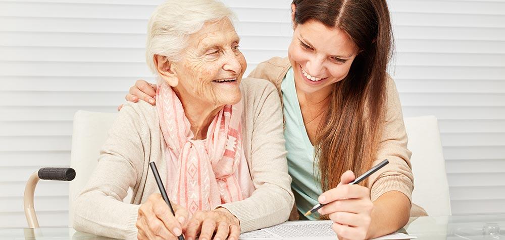 Senior Woman Writing With Caregiver