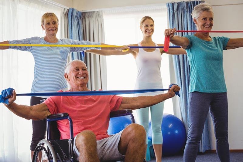 Seniors Stretching with Caregiver